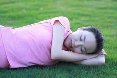 La donna cinese asiatica felice si rilassa su erba Fotografia Stock Libera da Diritti