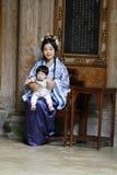 La donna cinese in vestito da Hanfu, tiene il suo bambino nel cheongsam Fotografie Stock Libere da Diritti