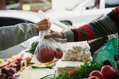 La donna compra le verdure ad un mercato fotografia stock