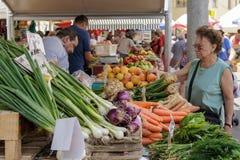 La donna compra le verdure al mercato immagine stock