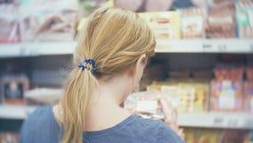 La donna compra una salsiccia in un supermercato, 4k stock footage