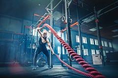 La donna con la battaglia della corda di battaglia ropes l'esercizio nella palestra di forma fisica fotografia stock libera da diritti