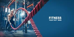 La donna con la battaglia della corda di battaglia ropes l'esercizio nella palestra di forma fisica fotografie stock