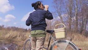 La donna con la bicicletta gode della festa vicino al lago in primavera stock footage