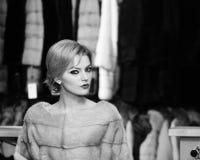 La donna con capelli biondi compra il cappotto simile a pelliccia Signora prova il soprabito grigio costoso del visone sopra Conc fotografie stock libere da diritti
