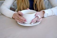 La donna con capelli biondi passa la tenuta della tazza bianca Fotografia Stock Libera da Diritti