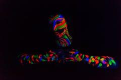 La donna con compone l'arte di polvere fluorescente UV d'ardore Fotografia Stock