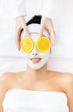 La donna con crema sul fronte e sull'arancia taglia sugli occhi Fotografie Stock Libere da Diritti
