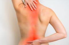La donna con dolore della spina dorsale sta tenendola che fa male indietro Immagini Stock