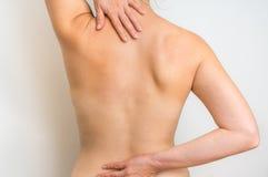 La donna con dolore della spina dorsale sta tenendola che fa male indietro Immagine Stock Libera da Diritti