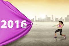 La donna con gli abiti sportivi tira i numeri 2016 Fotografia Stock Libera da Diritti