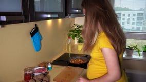 La donna con la grande pancia prepara la cena in cucina video d archivio