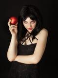 La donna con Halloween compone la mela di colore rosso della holding Fotografia Stock Libera da Diritti