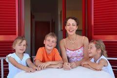 La donna con i bambini si siede di numero sulla veranda Fotografia Stock Libera da Diritti