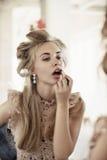 La donna con i bigodini nello specchio corregge il trucco fotografia stock