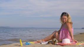 La donna con i cani sta riposando sulla spiaggia stock footage