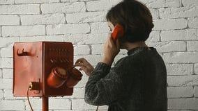 La donna con i capelli di scarsità compone in retro telefono video d archivio