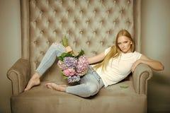 La donna con i fiori dell'ortensia si rilassa sul sofà Immagine Stock