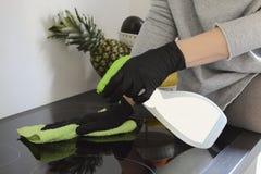 La donna con i guanti protettivi di gomma pulisce la stufa, piatto di induzione nella cucina con il liquido di pulizia per la pul fotografie stock
