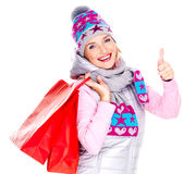 La donna con i pollici di manifestazioni dei sacchetti della spesa aumenta il segno Fotografia Stock