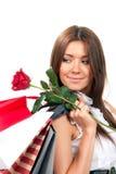 La donna con i sacchetti di acquisto ed il singolo colore rosso sono aumentato Immagini Stock Libere da Diritti