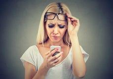 La donna con i vetri che hanno difficoltà che vede il telefono cellulare ha problemi della visione Tecnologia confusionaria fotografie stock