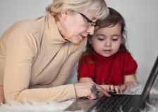 La donna con il bambino al calcolatore Immagini Stock Libere da Diritti