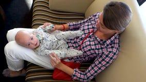 La donna con il bambino nel suo rivestimento sta sedendo sul sofà stock footage