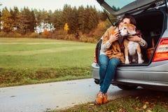 La donna con il cane si siede nel tronco di automobile sulla strada di autunno Fotografia Stock