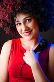 La donna con il canto dell'acconciatura di afro nel karaoke Fotografie Stock