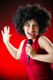 La donna con il canto dell'acconciatura di afro nel karaoke Fotografia Stock Libera da Diritti