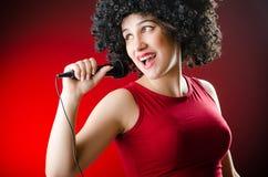La donna con il canto dell'acconciatura di afro nel karaoke Immagine Stock