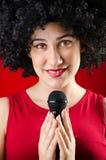 La donna con il canto dell'acconciatura di afro nel karaoke Fotografie Stock Libere da Diritti