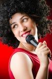 La donna con il canto dell'acconciatura di afro nel karaoke Immagine Stock Libera da Diritti