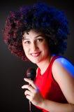 La donna con il canto dell'acconciatura di afro nel karaoke Immagini Stock Libere da Diritti