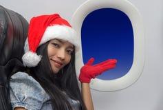 La donna con il cappello Santa Claus vola in aereo Immagini Stock