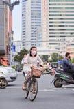 La donna con il cappuccio della bocca cicla nel traffico occupato, Kunmin, Cina Fotografia Stock Libera da Diritti