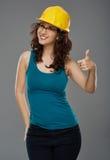 La donna con il casco della protezione che fa i pollici aumenta il segno Fotografia Stock