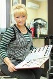 La donna con il catalogo dei colori dei capelli si siede sulla presidenza Fotografie Stock Libere da Diritti
