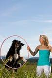 La donna con il cerchio di hula, cane salta attraverso Fotografia Stock