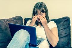 La donna con il computer portatile che ha stanco e ferita osserva Fotografia Stock