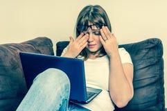 La donna con il computer portatile che ha stanco e ferita osserva Fotografia Stock Libera da Diritti
