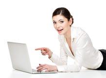 Donna con i punti del computer portatile allo schermo Fotografia Stock