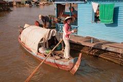 La donna con il crogiolo di pagaia funziona, otchalivaya dalla casa sull'acqua Fotografia Stock