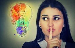 La donna con il dito sulle labbra gesture esaminando la lampadina della luce intensa fotografia stock libera da diritti