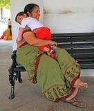 La donna con il figlio sta sedendo su un banco Fotografie Stock Libere da Diritti