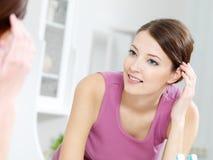 La donna con il fronte fresco pulito si leva in piedi circa uno specchio Fotografia Stock Libera da Diritti