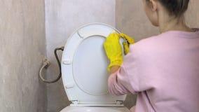La donna con il guanto di gomma giallo pulisce la toilette stock footage