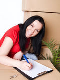 La donna con il pacchetto firma il documento di consegna Immagini Stock