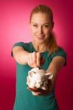 La donna con il porcellino salvadanaio in mani ha eccitato alla cassaforte per conservare il risparmio Immagine Stock Libera da Diritti